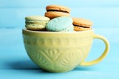 Assortment of gentle colorful macaroons in colorful mug on color wooden background — Stock Photo