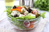 Greek salad in glass dish on napkin and color wooden background — Stock Photo