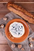 Blue cheese on earthenware dish with nuts and baguette on burlap cloth and wooden table background — Stock Photo