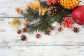 Fruits with spices and Christmas pine sprig — Stock Photo