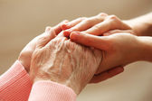 Old and young holding hands — Stock Photo