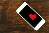 Smart mobile phone with red heart — Stock Photo