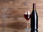 Red wine on table on wooden background — Stock Photo