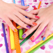 Multicolor female manicure with markers and pencils on bright background — Stock Photo #62384211