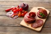 Sliced salami with chili pepper, cherry tomatoes, onion and spices on cutting board and wooden table background — Stock Photo