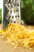 Grated cheese with grater and vegetables on wooden cutting board and white background — Stock Photo