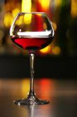 Glass of wine with bar on background — Stock Photo