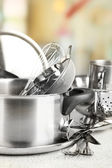 Stainless steel kitchenware on table, on light background — Stock Photo