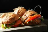 Sandwiches with salmon on tray, on dark background — Stock Photo