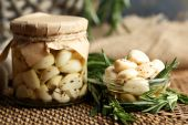 Canned garlic in glass jar and wicker mat and rosemary branches, on wooden background — Stock Photo