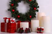 Christmas decoration with wreath, candles and present boxes on shelf on white wall background — Stock Photo