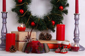 Christmas decoration with wreath, candles and present boxes on shelf on white wall background — Fotografia Stock