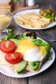Tosty z jajka Benedykta i awokado na tabliczce na drewnianym stole — Zdjęcie stockowe