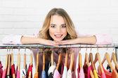 Woman near rack with hangers — Stock Photo