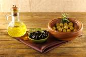 Composition of two round bowls with green and black olives near the oil can on silk cloth, on rustic wooden table, on burlap background — Stock Photo