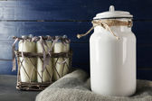 Milk can and glass bottles on color wooden background — Stock Photo