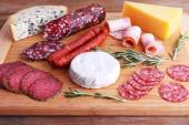 Assortment of smoked sausages and cheese on cutting board and wooden table background — Stock Photo