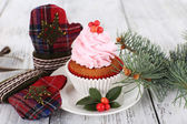Cup-cake on saucer with Christmas decoration on color wooden table background — Stock Photo