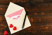 Envelope with hearts and pen on rustic wooden table background — Stock fotografie