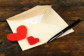 Envelope with hearts and pen on rustic wooden table background — Stockfoto