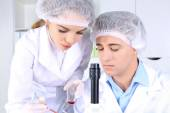Male and female scientists with microscope in laboratory — Stock Photo