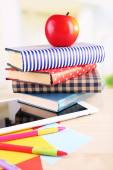 Pile of books with tablet on wooden table and light background — Foto de Stock