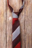 Stripped tie on wooden planks background — Stock Photo