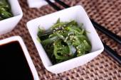 Seaweed salad with say sauce on wicker mat background — Stock Photo