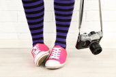 Girl in sneakers with retro photo camera in room — Stock Photo