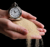 Silver pocket clock in hands and sand flowing away on black background — Stock Photo