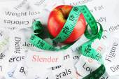 Papers with different words, apple and measuring tape close up — Foto de Stock