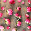 Beautiful pink dried roses on old wooden background — Stock Photo #62560413
