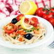 Tasty pasta with shrimps, black olives and tomato sauce on plate on wooden background — Stock Photo #62560823