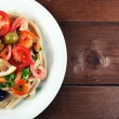 Tasty pasta with shrimps, mussels, black olives and tomato sauce on plate on wooden background — Stock Photo #62560835