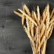 Spikelets of wheat on dark wooden background — Stock Photo #62560887