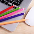 Laptop with computer mouse and colorful pencils on wooden table background — Stock Photo #62563079
