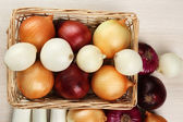Different raw onion on wooden background — Stock Photo