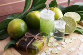 Spa composition with lime on wooden plate and wooden table background — Stock Photo