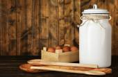 Milk can with eggs and spoons on rustic wooden background — Stock Photo