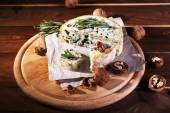 Blue cheese with sprigs of rosemary and nuts on board with sheet of paper and wooden table background — ストック写真