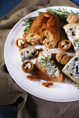 Blue cheese with sprigs of rosemary, bread and nuts on plate with burlap cloth and color wooden table background — Stock Photo