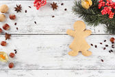 Christmas pine sprig with spices and gingerbread on color wooden background — Stock Photo