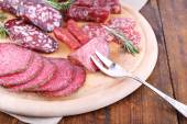Assortment of sausages on cutting board with burlap cloth and wooden table background — Foto de Stock