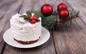 Delicious cake on saucer with holly and berry on Christmas decoration and wooden background — Stock Photo