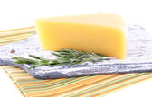 Chunk of Parmesan cheese on wooden cutting board with sprig of rosemary on napkin isolated on white — Stock Photo