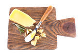 Crumbled Parmesan cheese with sprig of rosemary and knife on cutting board isolated on white — Stock Photo