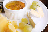 Different sort of cheese with grape and saucer on plate on wooden table background — Stockfoto
