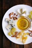 Different sort of cheese with grape, nuts and saucer on plate on wooden table background — Stockfoto