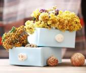 Dried flowers in chest on bright background — Stock Photo