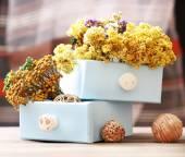 Gedroogde bloemen in borst op lichte achtergrond — Stockfoto
